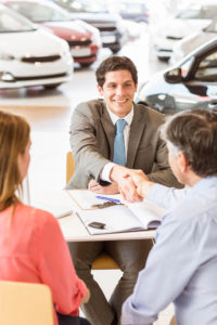 Couple at car dealer's desk shaking hands like they have a deal