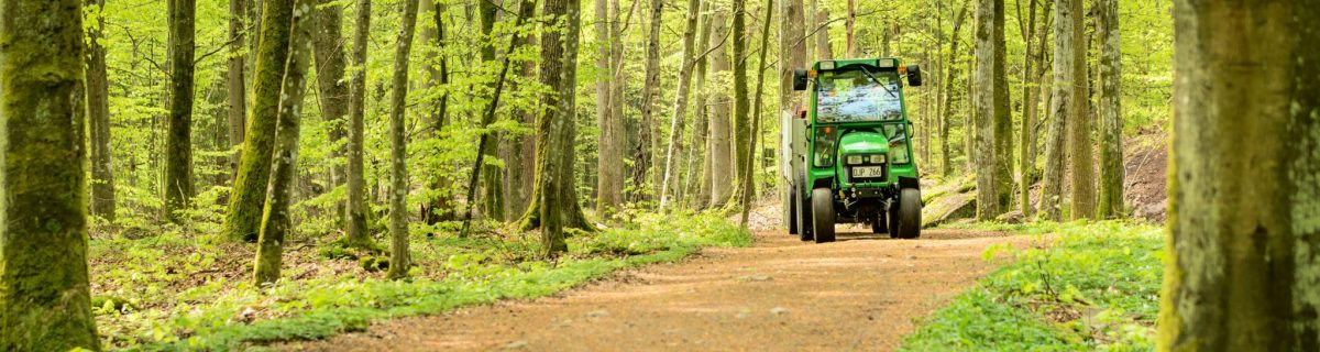 John Deere compact tractor on dirt road surrounded by trees