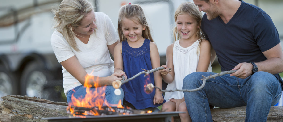 A family of four are roasting marshmallows together around a campfire while on vacation. Their RV is parcked in the background of the picture.