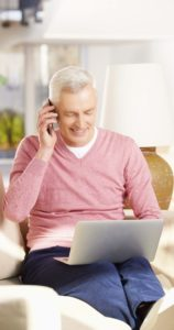 Elderly man working on computer with cell phone to his ear, smiling.