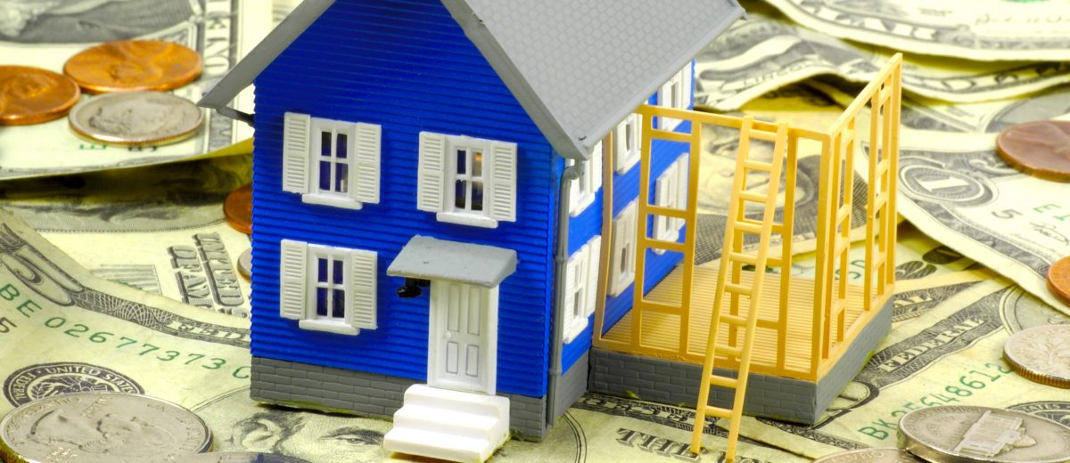 Miniature House sitting on Money depicting there is Equity in the house