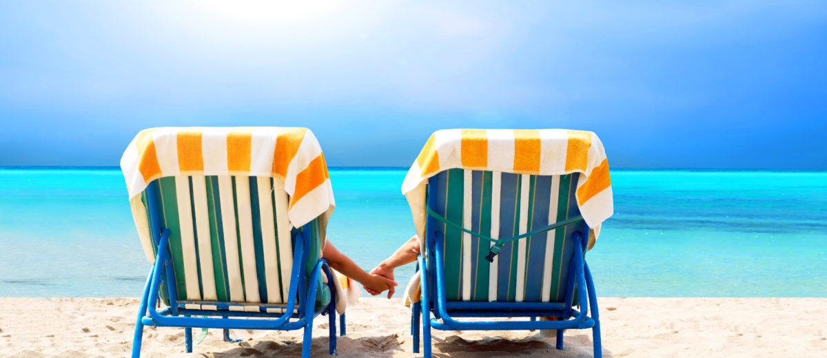 Two beach chairs facing ocean depiction vacation on beach