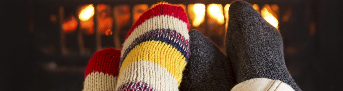 Couple's feet in woolen stocking in front of fire warming up