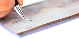 Closeup of person's hand writing a check