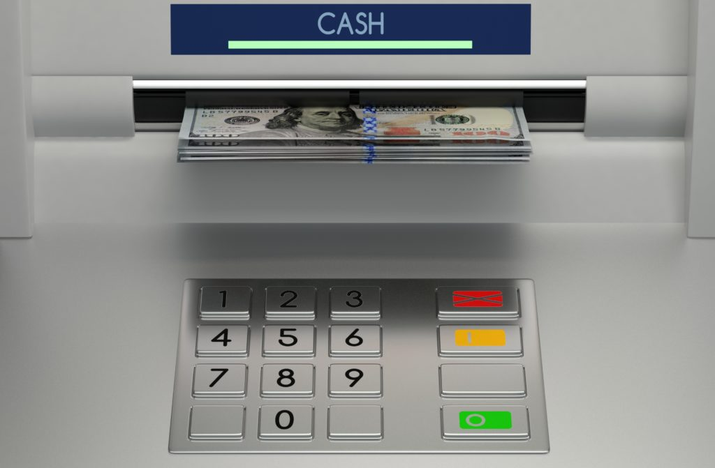 Photo of ATM with $100 bills coming out of a slot.