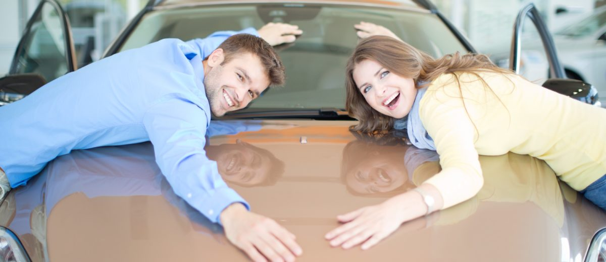 Happy couple embracing car in dealership and looking at camera.