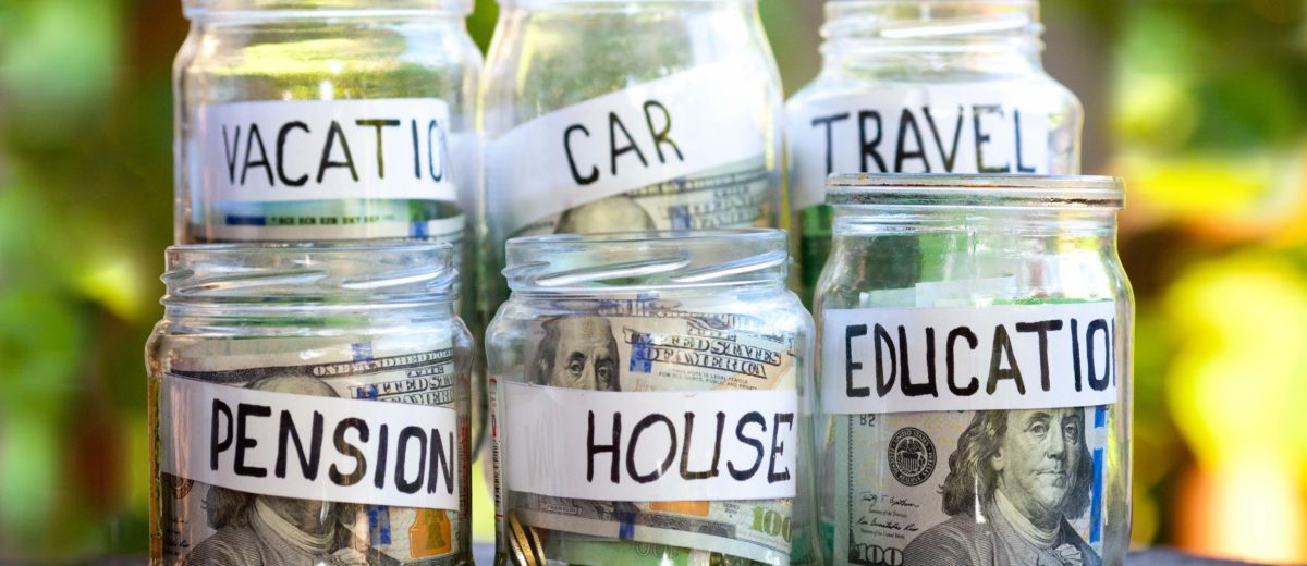 Money jars with money in each with tags that read vacation, car, travel, pension, house and education.