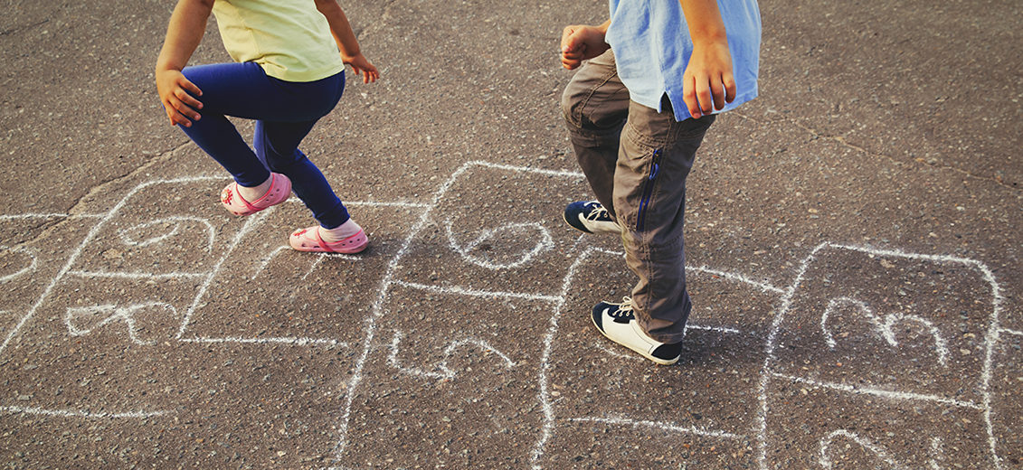 kids playing and skipping hopscotch on playground